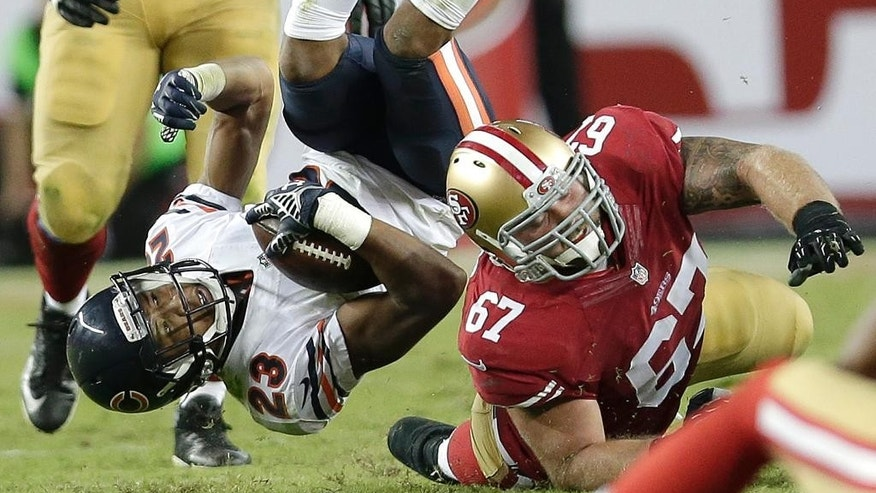 Chicago Bears cornerback Kyle Fuller (23) falls to the ground in front of San Francisco 49ers guard Daniel Kilgore (67) after intercepting quarterback Colin Kaepernick during the fourth quarter of an NFL football game in Santa Clara, Calif., Sunday, Sept. 14, 2014. (AP Photo/Marcio Jose Sanchez)