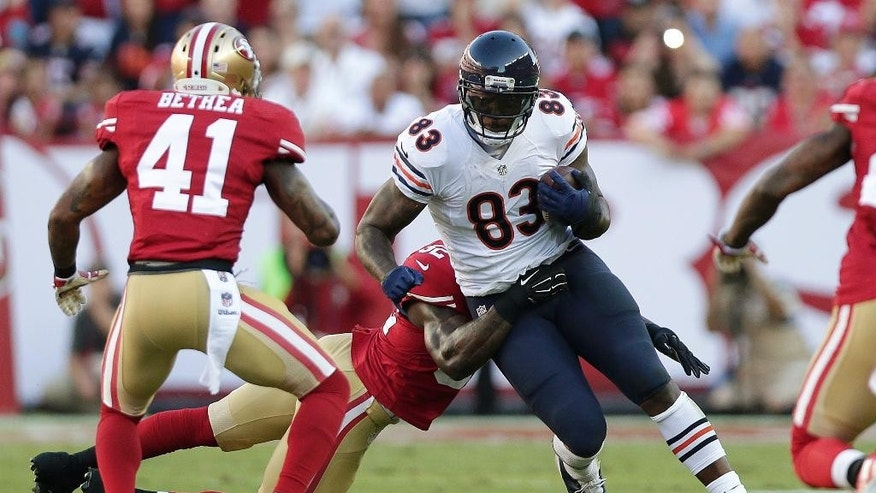 Chicago Bears cornerback Kyle Fuller (23) returns an interception past San Francisco 49ers guard Mike Iupati (77) during the fourth quarter of an NFL football game in Santa Clara, Calif., Sunday, Sept. 14, 2014. (AP Photo/Tony Avelar)