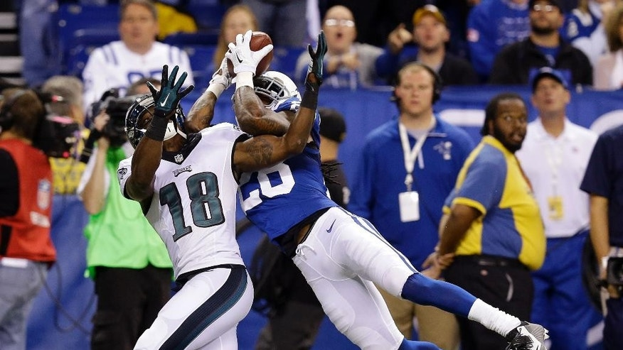 Indianapolis Colts Greg Toler makes an interception against Philadelphia Eagles wide receiver Jeremy Maclin (18) during the first half of an NFL football game Monday, Sept. 15, 2014, in Indianapolis. (AP Photo/Michael Conroy)