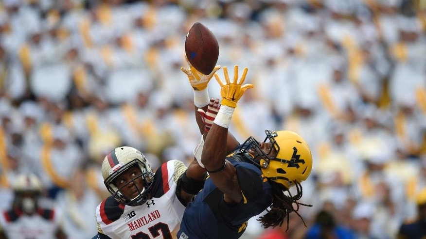 Maryland defensive back Alvin Hill, left, breaks up a pass intended for West Virginia wide receiver Kevin White, right, during the first half of an NCAA football game, Saturday, Sept. 13, 2014, in College Park, Md. (AP Photo/Nick Wass)