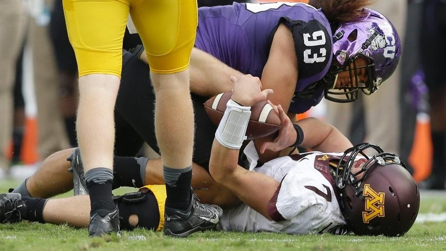 Minnesota quarterback Mitch Leidner (7) takes a hard hit from TCU defensive end Mike Tuaua (93) during the second half of an NCAA college football game, Saturday, Sept. 13, 2014, in Fort Worth, Texas.  Leidner left the game after the play. TCU won 30-7. (AP Photo/LM Otero)