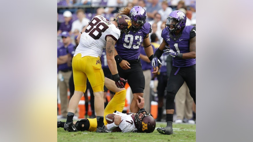 Minnesota quarterback Mitch Leidner (7)  lays on the ground after taking a hard hit from TCU defensive end Mike Tuaua (93) as teammate tight end Maxx Williams (88)  and TCU safety Chris Hackett (1) look on during the second half of an NCAA college football game, Saturday, Sept. 13, 2014, in Fort Worth, Texas.  Leidner left the game after the play. TCU won 30-7. (AP Photo/LM Otero)