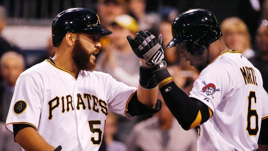 Pittsburgh Pirates' Russell Martin (55) celebrates with Starling Marte (6) as he returns to the dugout after hitting a two-run home run off Boston Red Sox starting pitcher Anthony Ranaudo during the second inning of a baseball game in Pittsburgh Tuesday, Sept. 16, 2014. (AP Photo/Gene J. Puskar)