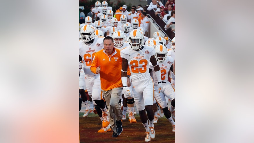 "FILE - In this Sept. 13, 2014, file photo, Tennessee head coach Butch Jones, second from left, runs onto the field with his team before an NCAA college football game against Oklahoma in Norman, Okla. Tennessee's Jones, Washington's Chris Petersen, Georgia's Mark Richt and Clemson's Dabo Swinney are among the coaches who have adopted ""The Energy Bus,"" a book that extols the power of positive thinking and warns to stay away from ""energy vampires."" (AP Photo/Sue Ogrocki, File)"