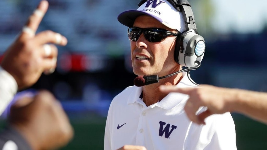 "FILE - In this Sept. 13, 2014, file photo, Washington head coach Chris Petersen stands on the sideline during an NCAA college football game against Illinois in Seattle. Washington's Petersen, Tennessee's Butch Jones, Georgia's Mark Richt and Clemson's Dabo Swinney are among the coaches who have adopted ""The Energy Bus,"" a book that extols the power of positive thinking and warns to stay away from ""energy vampires."" (AP Photo/Ted S. Warren, File)"