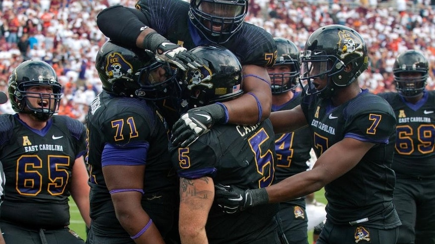 FILE - In this Sept. 13, 2014, file photo, East Carolina players, J.T. Boyd (65) Dontae Levingston (71) Shane Carden (5) Isaiah Jones (7) and Quincy McKinney (72) celebrate the winning touchdown during an NCAA college football game against Virginia Tech in Blacksburg, Va. East Carolina has long played a nonconference schedule loaded up with prominent names and power-conference opponents.  (AP Photo/Don Petersen, File)
