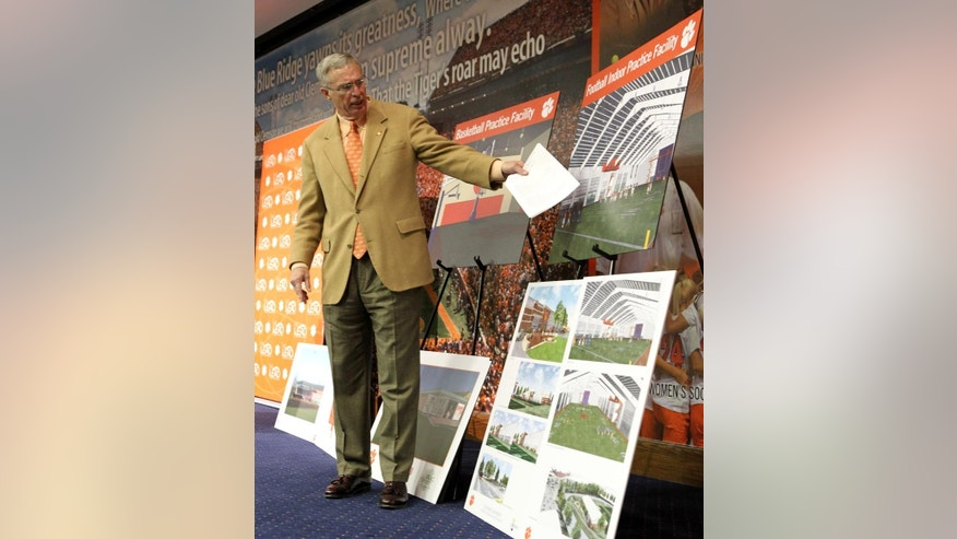 FILE - In this Jan. 14, 2011, file photo, Clemson athletic director Dr. Terry Don Phillips points at an architectural rendering of a proposed indoor football practice facility during a news conference in Clemson, S.C., where the university's athletic department announced their goal to invest $50 million over the next five years in capital projects. The master plan includes enhancements to facilities for football, baseball, basketball, soccer, tennis and golf.  Clemson opened the new indoor practice facilities in 2013. (AP Photo/Anderson Independent-Mail, Mark Crammer, File) THE GREENVILLE NEWS OUT, SENECA NEWS OUT.