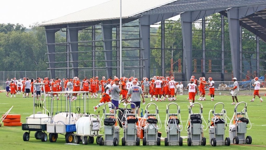FILE - In this Aug. 3, 2012, file photo, water dispensers line the field as the Clemson football team works out next to their under-construction new indoor practice facility on the first day of NCAA college football practice  in Clemson, S.C. During the past 18 months, half the Atlantic Coast Conference  schools have either begun or completed major projects to upgrade their football facilities.  Clemson opened the new indoor practice facilities in 2013. (AP Photo/Anderson Independent-Mail, Mark Crammer, File) GREENVILLE NEWS OUT; SENECA NEWS OUT