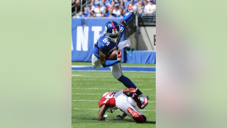 New York Giants tight end Larry Donnell (84) leaps over Arizona Cardinals' Tony Jefferson (22) during the first half of an NFL football game Sunday, Sept. 14, 2014, in East Rutherford, N.J.  (AP Photo/Bill Kostroun)