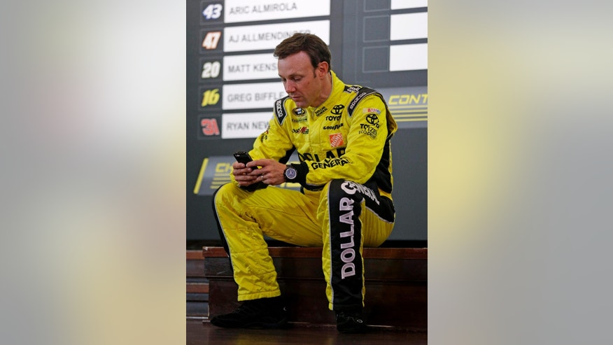Matt Kenseth checks his phone during the NASCAR Sprint Cup media day in Chicago, Thursday, Sept. 11, 2014. The 16 drivers in the Chase for the Sprint Cup championship took part in the event. The opening race in the Chase is at Chicagoland Speedway on Sunday in Joliet, Ill. (AP Photo/Nam Y. Huh)