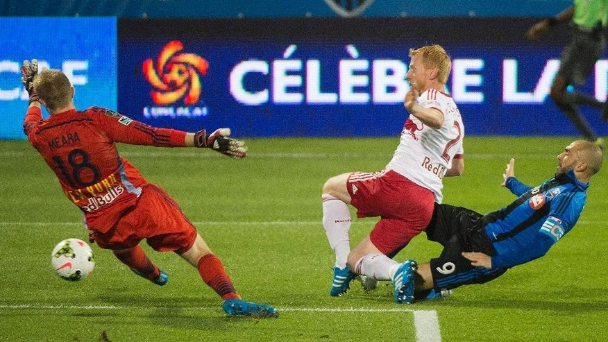 Montreal Impact's Marco Di Vaio, right, scores against New York Red Bulls' goalkeeper Ryan Meara, left, as Red Bulls' Richard Eckersley defends during the first half of a CONCACAF Champions League soccer game, Wednesday, Sept. 17, 2014  in Montreal, (AP Photo/The Canadian Press, Graham Hughes)