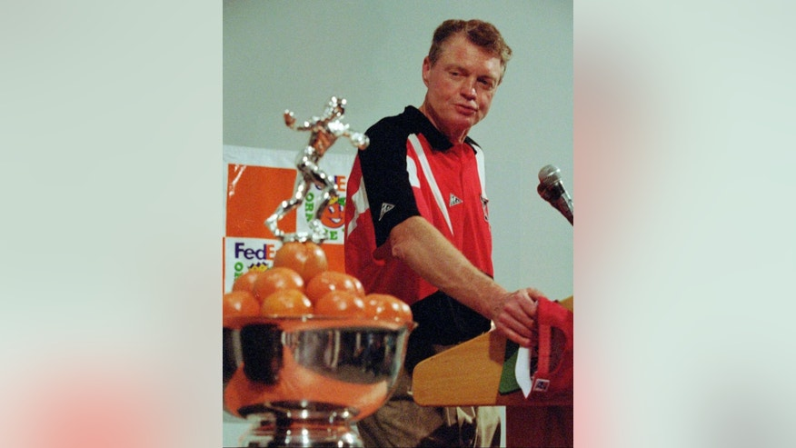 FILE - In this J an. 1, 1995, file photo, Nebraska coach Tom Osborne looks at the NCAA college football FedEx Orange Bowl trophy during a post-game news conference in Miami. Top-ranked Nebraska defeated Miami 24-17. The Miami and Nebraska programs are but a shell of their former selves as they enter Saturday night's game in Lincoln. (AP Photo/Hans Deryk, File)