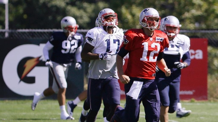 New England Patriots quarterback Tom Brady (12) and wide receiver Aaron Dobson (17) run during a stretching session before practice begins at the NFL football team's facility Wednesday, Sept. 17, 2014 in Foxborough, Mass. (AP Photo/Stephan Savoia)