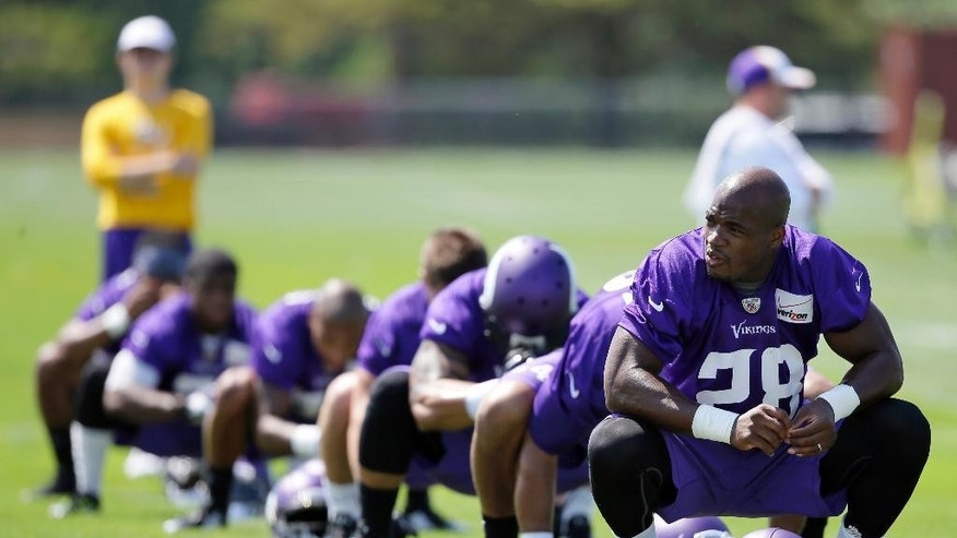 FILE - In this July 26, 2014, file photo,Minnesota Vikings running back Adrian Peterson, right, stretches during NFL football training camp in Mankato, Minn. After a day of public pressure from angry fans and concerned sponsors, the Vikings have reversed course and placed star  Peterson on the exempt-commissioner's permission list, the team announced Wednesday, Sept. 17, 2014. The move that will require him to stay away from the team while he addresses child abuse charges in Texas. (AP Photo/Charlie Neibergall, File)