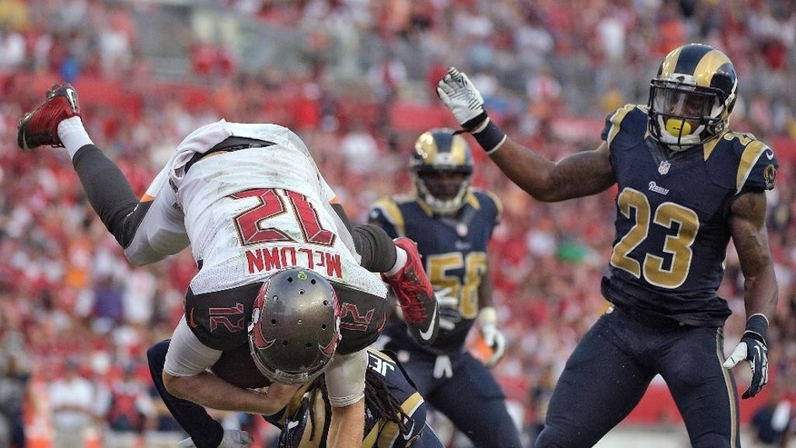 Tampa Bay Buccaneers quarterback Josh McCown (12) is upended by St. Louis Rams cornerback Janoris Jenkins (21) as he dives over the goal line to score on a 1-yard touchdown run during the third quarter of an NFL football game Sunday, Sept. 14, 2014, in Tampa, Fla. Defending for the Rays is free safety Rodney McLeod (23). (AP Photo/Phelan M. Ebenhack)