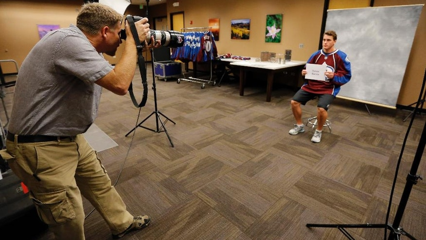 Colorado Avalanche team photographer Michael Martin takes a photograph of Tyson Barrie during NHL hockey media day Thursday, Sept. 18, 2014, in Denver. (AP Photo/Jack Dempsey)