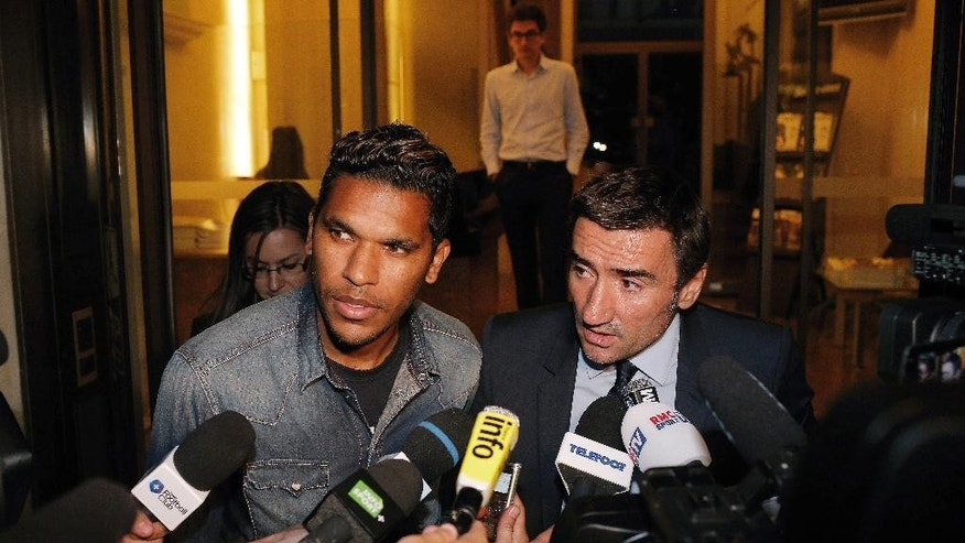 Brazilian striker Brandao, left, and his lawyer Olivier Martin answer media as they leaves the French league disciplinary hearing, in Paris, Thursday, Sept. 18, 2014. Brandao attends a French league disciplinary hearing for headbutting Paris Saint-Germain midfielder Thiago Motta and breaking his nose after a match between PSG and Bastia last month. He has already been provisionally suspended but could face a lengthy ban. (AP Photo/Thibault Camus)