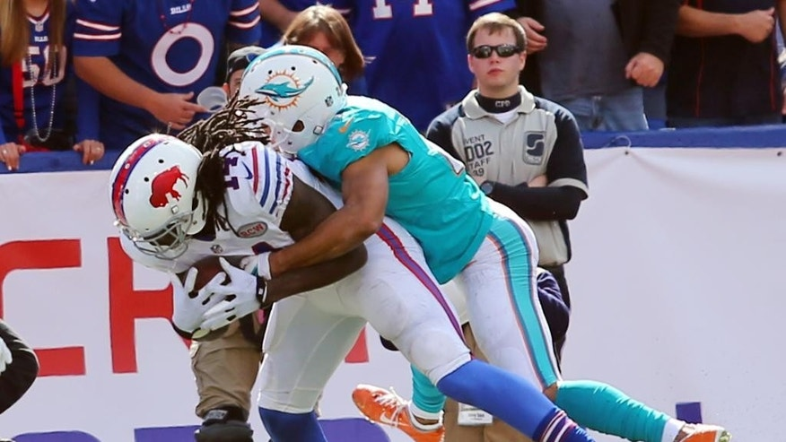 Buffalo Bills wide receiver Sammy Watkins (14) scores a touchdown as he is tackled by Miami Dolphins cornerback Brent Grimes during the second half of an NFL football game on Sunday, Sept. 14, 2014, in Orchard Park, N.Y. (AP Photo/Bill Wippert)