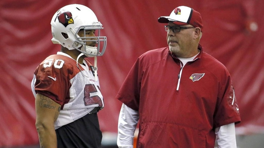 Arizona Cardinals head coach Bruce Arians, right, talks with linebacker Larry Foote (50) during NFL football practice, Thursday, Sept. 18, 2014, at the teams' training facility in Tempe, Ariz. It was the first day of practice after running back Jonathan Dwyer was arrested on aggravated assault charges and deactivated from all team activities. (AP Photo/Matt York)
