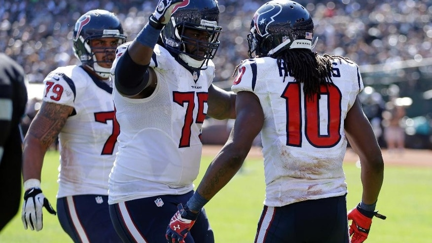 Houston Texans wide receiver DeAndre Hopkins (10) is greeted by teammates Derek Newton (75) and Brandon Brooks (79) after scoring a touchdown on a 12-yard pass in the third quarter of an NFL football game against the Oakland Raiders, Sunday, Sept. 14, 2014, in Oakland, Calif. (AP Photo/Ben Margot)