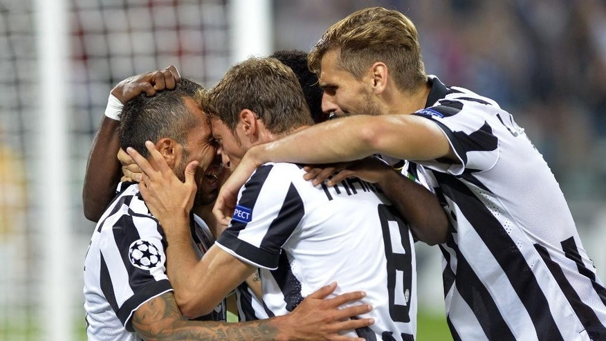 Juventus' Carlos Tevez, left, celebrates with teammates after scoring during a Champions League, Group A soccer match between Juventus and Malmoe, at the Juventus Stadium in Turin, Italy, Tuesday, Sept. 16, 2014. (AP Photo/Massimo Pinca)