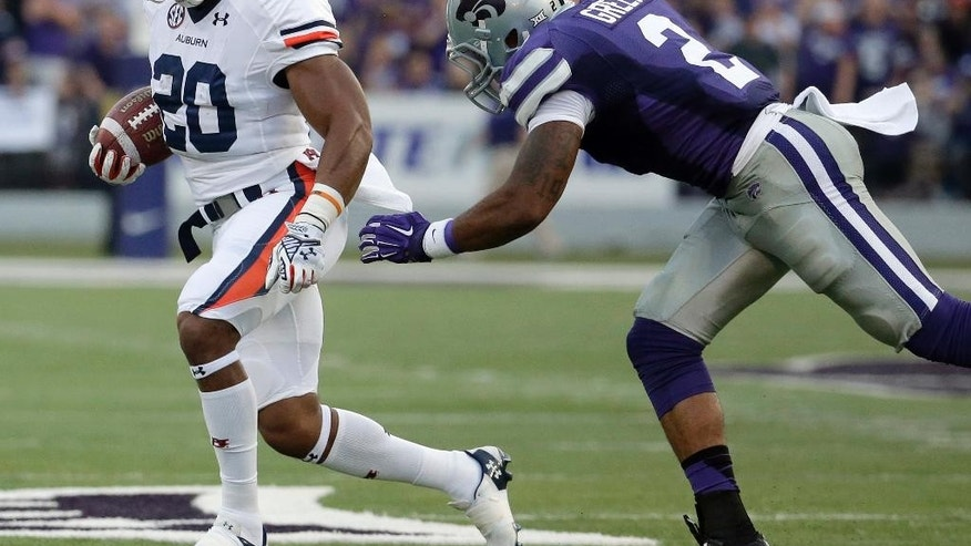 Auburn running back Corey Grant (20) tries to get past Kansas State defensive back Travis Green (2) during the first half of an NCAA college football game Thursday, Sept. 18, 2014, in Manhattan, Kan. (AP Photo/Charlie Riedel)