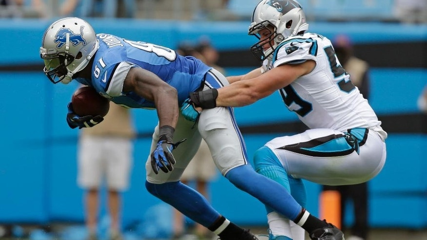 Carolina Panthers' Cam Newton (1) is sacked by Detroit Lions' C.J. Mosley (99) during the second half of an NFL football game in Charlotte, N.C., Sunday, Sept. 14, 2014. (AP Photo/Bob Leverone)