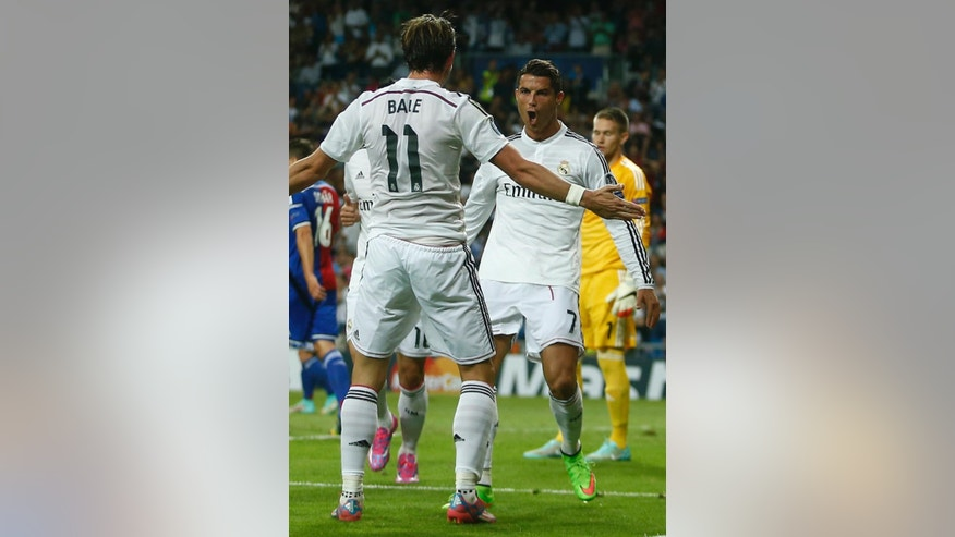 Real Madrid's Cristiano Ronaldo celebrates with teammate Gareth Bale after scoring his side's third goal during the Champions League Group B soccer match between Real Madrid and Basel at the Santiago Bernabeu stadium in Madrid, Spain, Tuesday Sept. 16, 2014. (AP Photo/Andres Kudacki)