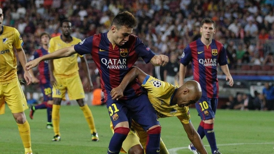 Barcelona's Munir El Haddadi, left, fights for the ball with APOEL's Da Cruz Junior during the Champions League Group F soccer match between Barcelona and Apoel at the Camp Nou stadium in Barcelona, Spain, Wednesday, Sept. 17, 2014. (AP Photo/Emilio Morenatti)