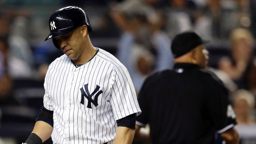 New York Yankees' Carlos Beltran, left, walks to the dugout after striking out looking to end a baseball game in a 1-0 loss to the Kansas City Royals, Friday, Sept. 5, 2014, in New York. (AP Photo/Julio Cortez)