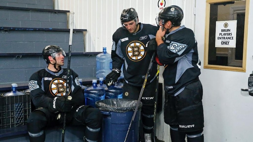 From left, Boston Bruins defenseman Johnny Boychuk, Patrice Bergeron, and left wing Brad Marchand chat as they wait for the ice to be cleared during NHL hockey training camp in Wilmington, Mass., Friday, Sept. 19, 2014. (AP Photo/Elise Amendola)