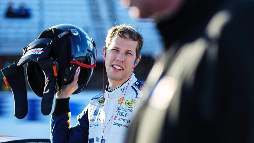 Driver Brad Keselowski listens with his headphones in the pit after having the fastest qualifying time earning the pole for the NASCAR Sprint Cup auto race at New Hampshire Motor Speedway, in Loudon, N.H., Friday, Sept. 19, 2014 (AP Photo/Cheryl Senter)