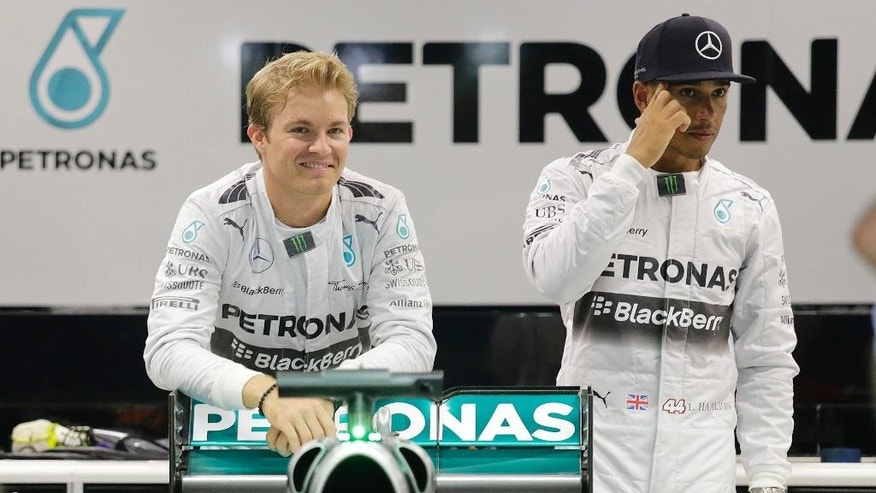 Mercedes drivers Lewis Hamilton of Britain, right and Nico Rosberg of Germany, wait for their photo to be taken in their team garage at the Marina Bay City Circuit for the Singapore Formula One Grand Prix in Singapore, Thursday, Sept. 18, 2014 in Singapore. The F1 race is scheduled for Sunday, Sept. 21.(AP Photo/Wong Maye-E)