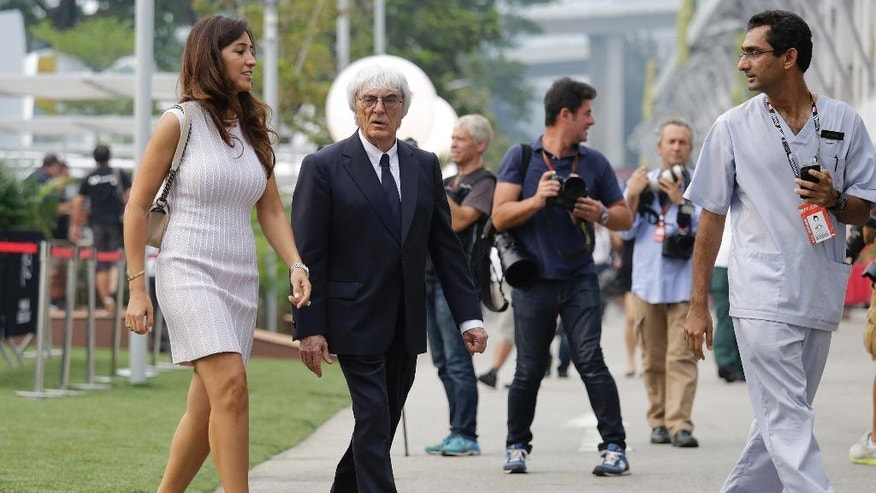 Formula One boss Bernie Ecclestone, center, walks with his wife, Fabiana Flosi, left, at the Marina Bay City Circuit for the Singapore Formula One Grand Prix, Thursday, Sept. 18, 2014. The F1 race is scheduled for Sunday, Sept. 21.(AP Photo/Wong Maye-E)