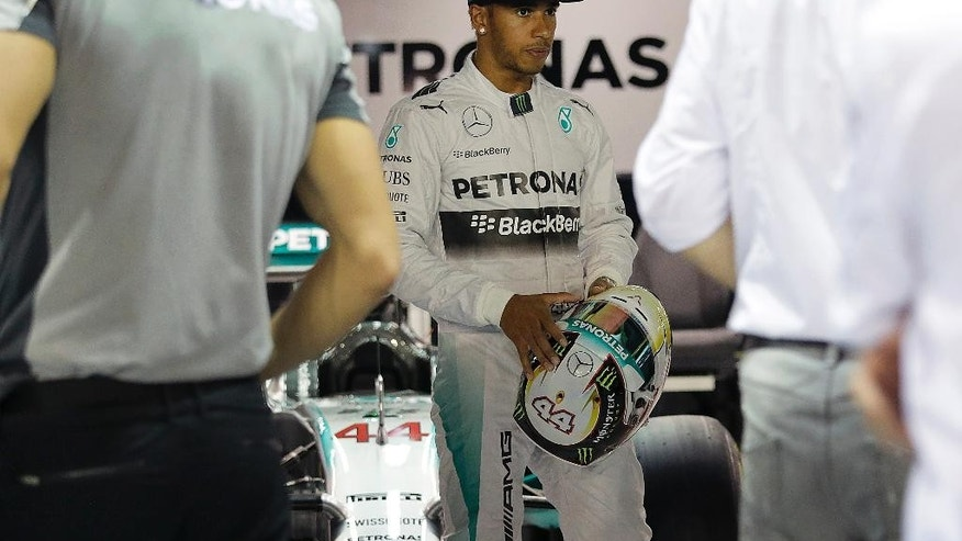 Mercedes driver Lewis Hamilton of Britain waits in his team garage at the Marina Bay City Circuit for the Singapore Formula One Grand Prix in Singapore, Thursday, Sept. 18, 2014 in Singapore. The F1 race is scheduled for Sunday, Sept. 21.(AP Photo/Wong Maye-E)