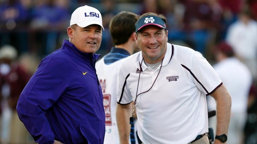 FILE - In this Oct. 5, 2013, file photo, LSU coach Les Miles, left, and Mississippi State coach Dan Mullen smile prior to an NCAA college football game in Starkville, Miss. The Bulldogs feel like they have the talent to end their 14 game losing streak against LSU on Saturday, but it won't be easy at Tiger Stadium.(AP Photo/Rogelio V. Solis, File)