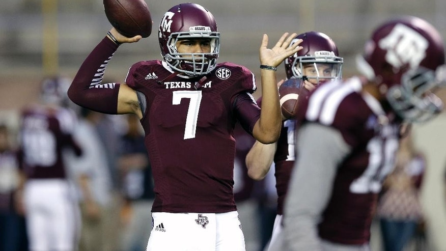 FILE - In this  Saturday, Sept. 13, 2014 file photo, Texas A&M quarterback Kenny Hill throws a pass before an NCAA college football game against Rice in College Station, Texas. Kenny Hill insists he wasn't daunted taking over for Johnny Manziel as quarterback at Texas A&M.  He did, however, ask the 2012 Heisman Trophy winner and one of the most popular college players in recent history for some advice.(AP Photo/David J. Phillip, File)