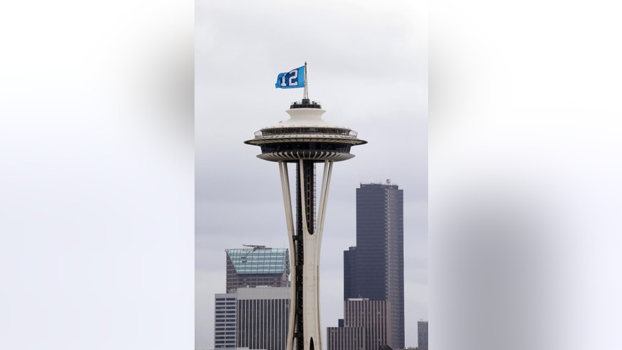 "FILE - In this Jan. 30, 2014, file photo, a ""12th Man"" flag, honoring Seattle Seahawks fans, billows in the wind atop the Space Needle in Seattle. Businesses through the upper left corner of the country are trying to capitalize the pride of the Seahawks fans. Whether it's getting Russell Wilson to be the pitchman for the local airline, to alcoholic beverages with 12 in the name, companies are finding ways to capitalize on the Super Bowl champs.(AP Photo/File)"