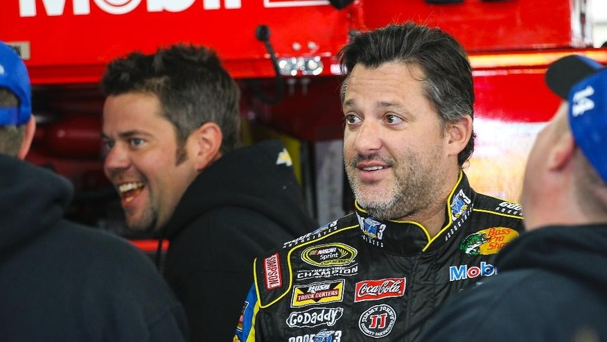 Driver Tony Stewart enjoys a light moment in his garage with crew members before practice for Sunday's NASCAR Sprint Cup auto race at New Hampshire Motor Speedway, Friday, Sept. 19, 2014, in Loudon, N.H.  (AP Photo/Cheryl Senter)