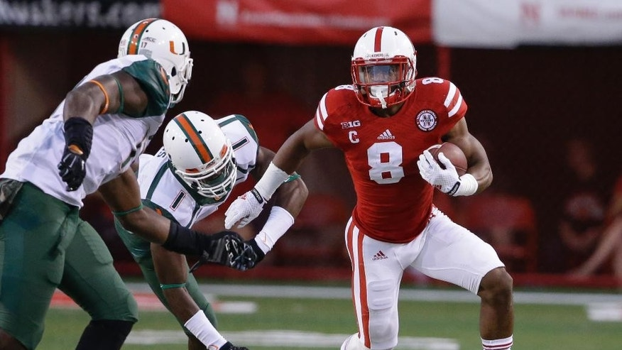 Nebraska running back Ameer Abdullah (8) runs away from Miami defensive back Artie Burns (1) and linebacker Tyriq McCord, left,  in the first half of an NCAA college football game in Lincoln, Neb., Saturday, Sept. 20, 2014. (AP Photo/Nati Harnik)