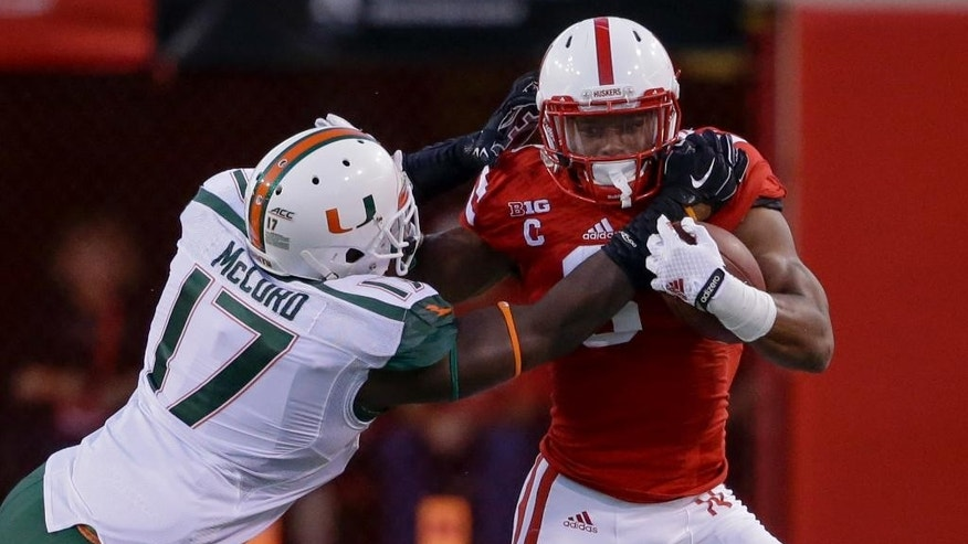 Nebraska running back Ameer Abdullah (8) runs past Miami linebacker Tyriq McCord (17) in the first half of an NCAA college football game in Lincoln, Neb., Saturday, Sept. 20, 2014. (AP Photo/Nati Harnik)