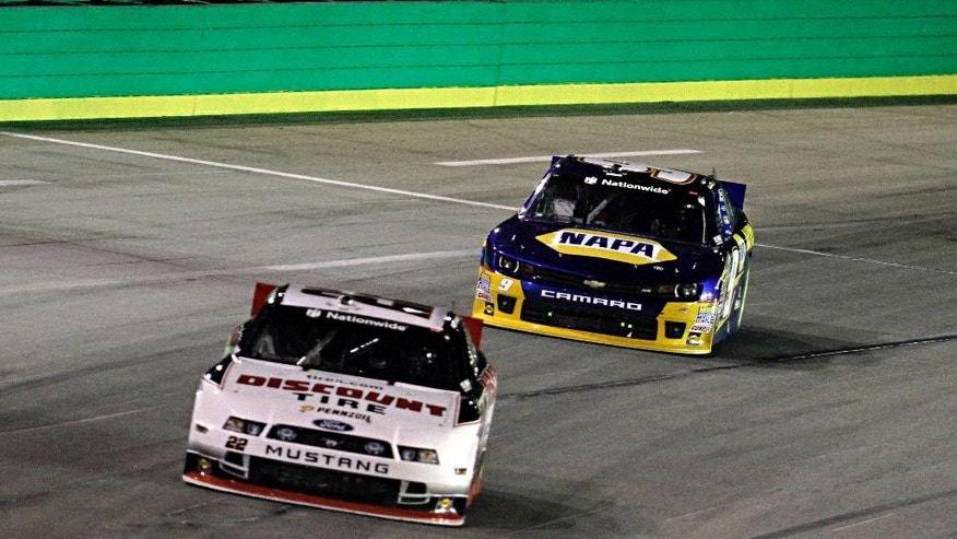 Points leader Chase Elliott (9) closes on Landon Cassill (22) to pass as he tries to catch race leader Ty Dillon in the NASCAR Nationwide auto race in Sparta, Ky., Saturday, Sept. 20, 2014. (AP Photo/Garry Jones)