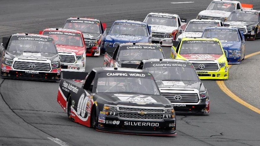 Cole Custer (00) grabs the lead on a restart during the NASCAR Camping World Truck Series at New Hampshire Motor Speedway, Saturday, Sept. 20, 2014, in Loudon, N.H. Custer went on to win the race. (AP Photo/Jim Cole)