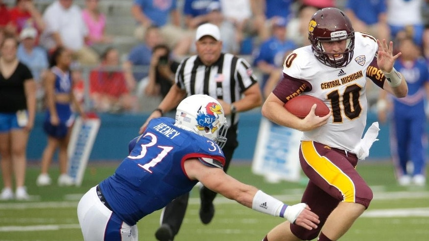 Central Michigan quarterback Cooper Rush (10) tries to get past Kansas linebacker Ben Heeney (31) during the first half of an NCAA college football game Saturday, Sept. 20, 2014, in Lawrence, Kan. (AP Photo/Charlie Riedel)