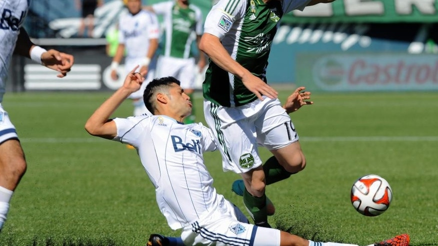 Vancouver Whitecaps' Matias Laba (15) battles the ball against Portland Timbers' Jorge Villafana (19) during the first half of an MLS soccer game in Portland, Ore., Saturday Sept., 20, 2014.  (AP Photo/Greg Wahl-Stephens)