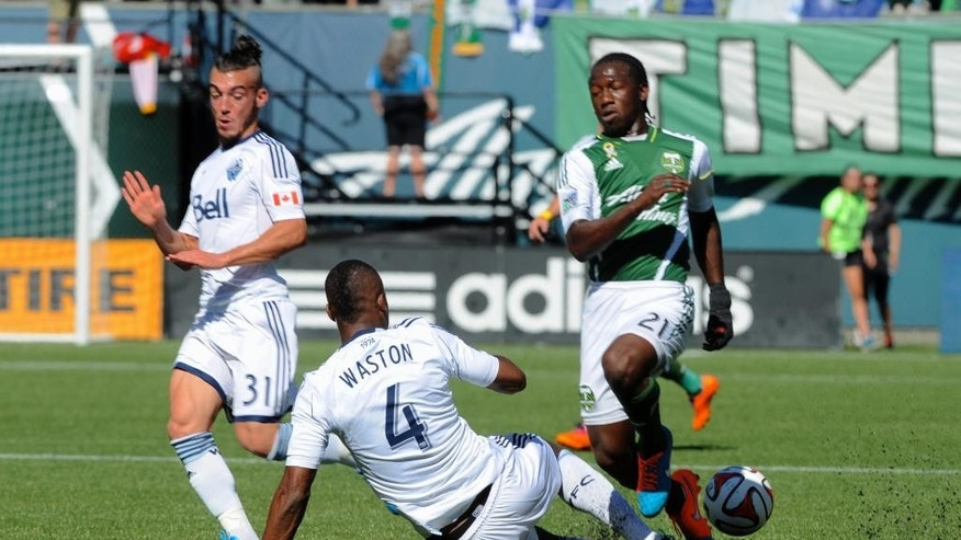 Vancouver Whitecaps' Kendall Waston (4) and Russell Teibert (31) defend against Portland Timbers'  Diego Chara (21) during the first half of an MLS soccer game in Portland, Ore., Saturday Sept., 20, 2014.  (AP Photo/Greg Wahl-Stephens)