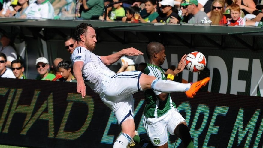 Vancouver Whitecaps' Andy O'Brien (40) defends against Portland Timbers' Darlington Nagbe (6) during the first half of an MLS soccer game in Portland, Ore., Saturday Sept., 20, 2014.  (AP Photo/Greg Wahl-Stephens)