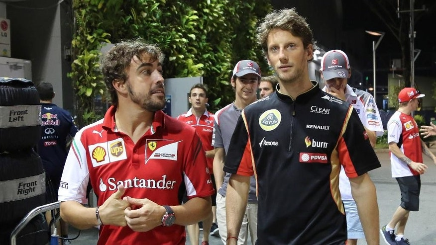 Ferrari driver Fernando Alonso of Spain, left, walks with Lotus driver Romain Grosjean of France, right, after the second practice session for the Singapore Formula One Grand Prix on the Marina Bay City Circuit in Singapore, Saturday, Sept. 20, 2014. (AP Photo/Aaron Favila)