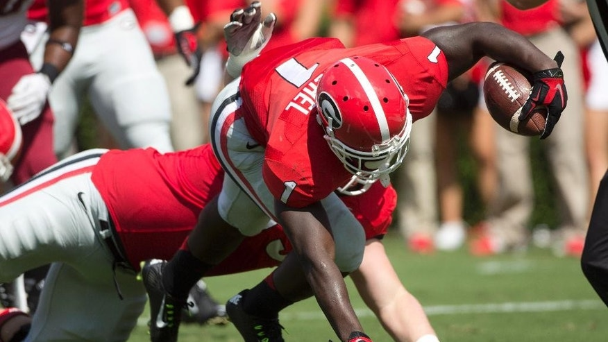 Georgia running back Sony Michel (1) scores with the help of offensive tackle Kolton Houston (75) in the first half of an NCAA college football game, Saturday, Sept. 20, 2014, in Athens, Ga. (AP Photo/John Bazemore)