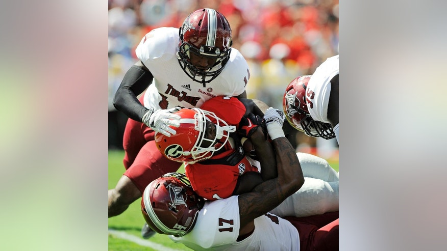 Georgia running back Sony Michel (1) pushes past Troy safety JaQuadrian Lewis (14), safety Rod Adams (17) and linebacker Mark Wilson (35) for a touchdown during the first half of an NCAA college football game in Athens, Ga., Saturday, Sept. 20, 2014. (AP Photo/Troy Messenger, Thomas Graning)